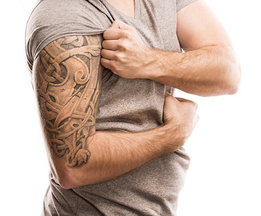 Handsome young man with tattoo, isolated on white.